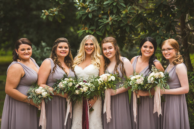 bride with bridesmaids in dusty purple dresses