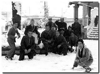 Niños y adultos divirtiéndose delante del Tablao de la Música de El Arenal, cuyos escalones cubre la nieve.