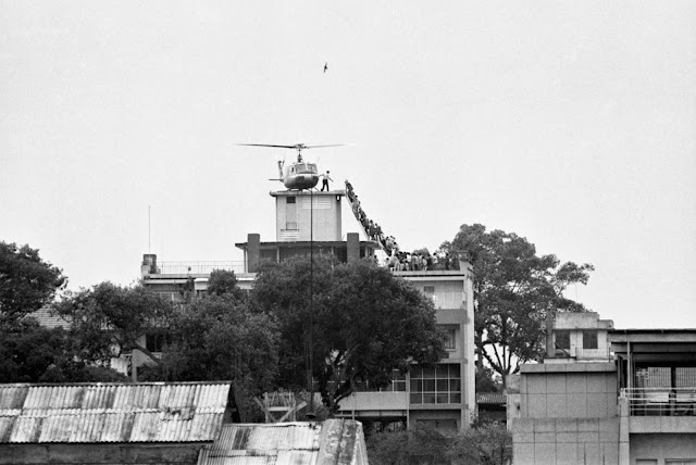 A CIA employee helps U.S. evacuees up a ladder onto an Air America Bell 204B helicopter, on the apartment building roof at 22 Gia Long Street, Saigon, shortly before the city's fall (April 29, 1975) Photo by Hubert van Es