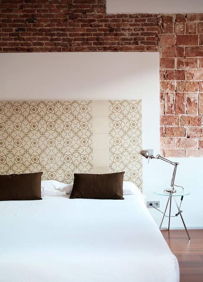 Dormitorio con azulejos hidraúlicos y pared de piedra