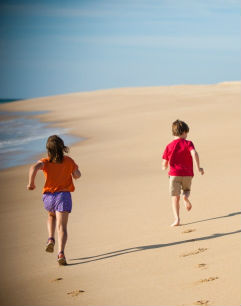Kids running on the sand at the beach