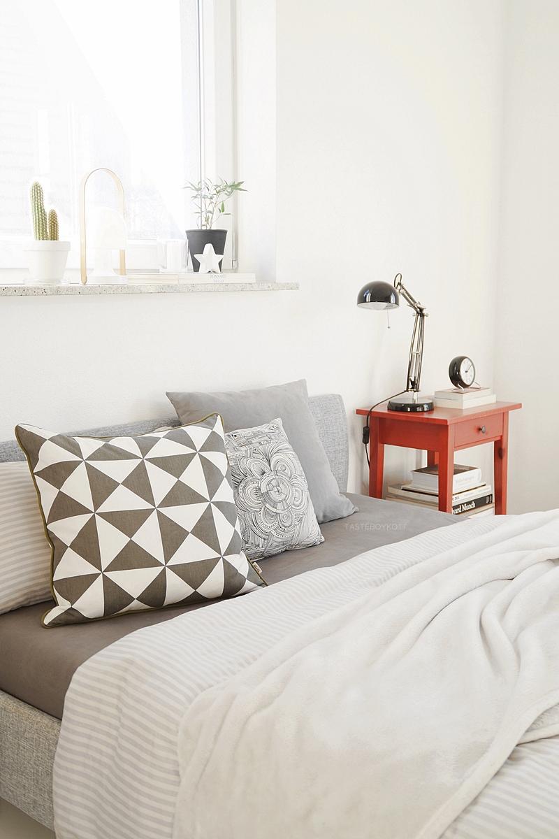 Minimalistisches weißes Schlafzimmer mit rotem Nachttisch als Farbtuper von Ikea, Kissen in Grau von Ferm Living im schlichten modernen skandinavischen Stil. Tasteboykott Wohnblog.