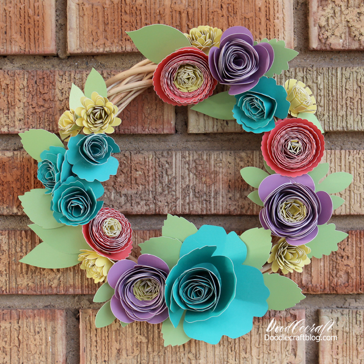 Make flowers with brightly colored paper rolled into 3D flowers and hot glued onto a wreath form.