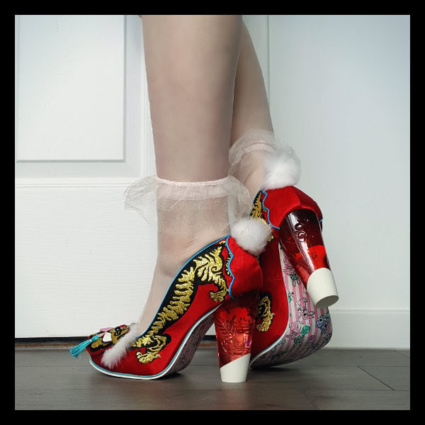 wearing Irregular Choice red Ruby Envelope court shoes showing fluffy pom pom