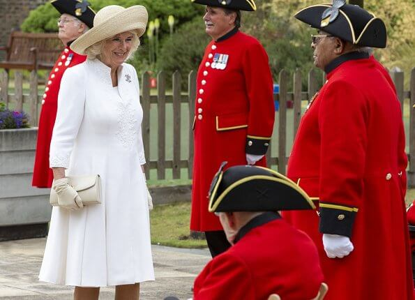 The Duchess of Cornwall wore a white embroidered coat dress with beige leather shoes, and beige hat and she carried beige clutch