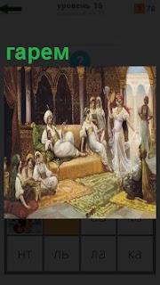 В большом помещение сидит султан на ковре и вокруг него гарем из девушек