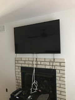 image of tv hung on wall with a wiring mess