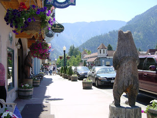 Das Meisterstuck storefront in Leavenworth, Washington, with a wooden carved bear on the sidewalk, parked cars and towering mountains in the background