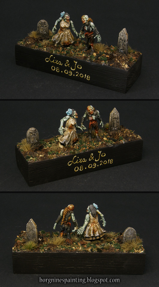Two zombie miniatures holding hands, standing on a large wooden base with two open graves, creating a small diorama. On the side of the base there's the names and the date of the people for whom the gift is.