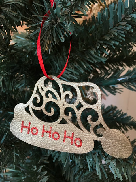 I used my Cricut to make a Santa hat Christmas ornament using faux leather and glitter iron on vinyl.