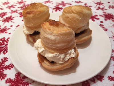 Three puff pastry mince pies filled with whipped cream on a plate.