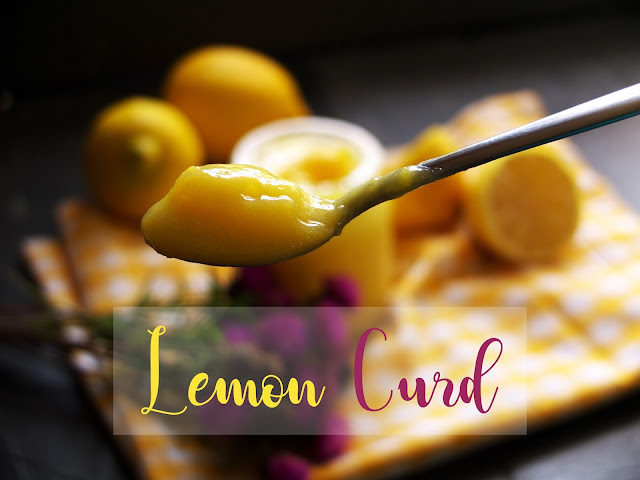 A spoon with lemon curd with a jar and lemons in the background.