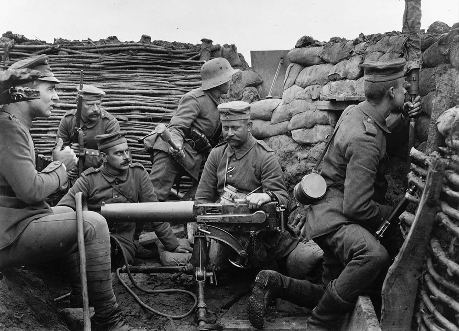 Six German soldiers pose in a in trench with machine gun, a mere 40 meters from the British line, according to the caption provided. The machine gun appears to be a Maschinengewehr 08, or MG 08, capable of firing 450-500 rounds a minute. The large cylinder is a jacket around the barrel, filled with water to cool the metal during rapid fire. The soldier at right, with gas mask canister slung over his shoulder, is peering into a periscope to get a view of enemy activity. The soldier at rear, with steel helmet, holds a