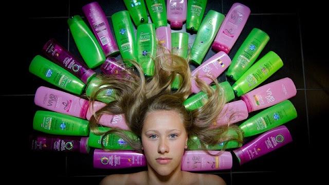 seorang gadis dikelilingi beragam merk dan jenis sampo