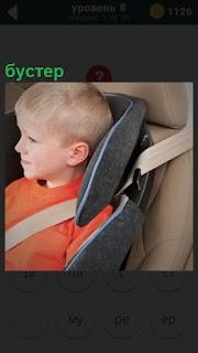 В авто кресле в автомобиле сидит ребенок,бустер его удерживает