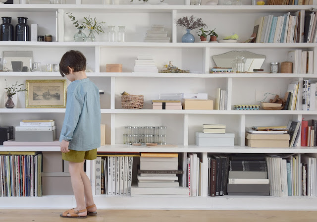 Child with white built in shelving wall in 1650 Marais Paris home of Lucille Gauthier-Braud