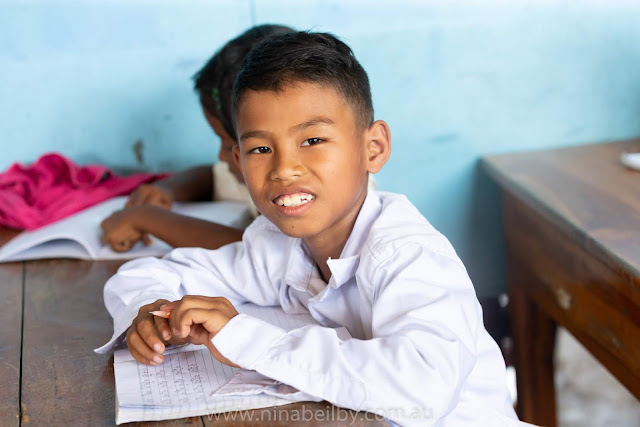 Male Cambodian child sitting at desk with his pencil and notebook, smiling.