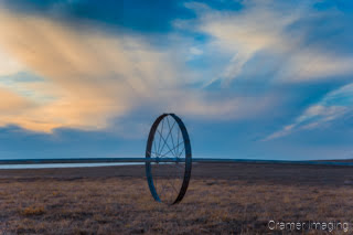 Cramer Imaging's fine art landscape photograph of wheel line irrigation equipment against a dramatic sunset sky in wintertime in Idaho