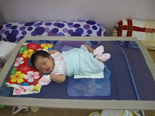 bé nằm ngủ rất ngoan trên giường lưới
