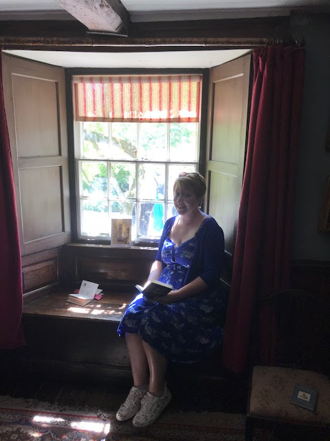 Woman sitting in a window seat with a book in her hand
