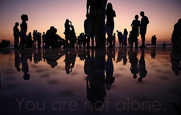 image of a group of people in silhouette on a beach at dusk, to which I've added text reading 'You are not alone.'