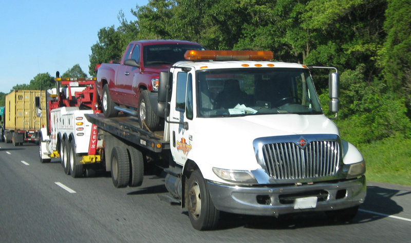Image of tow truck with truck on bed being towed