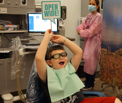 "young boy sitting in a clinic chair holding up a sign ""open wide"" Dental student in background smiling."
