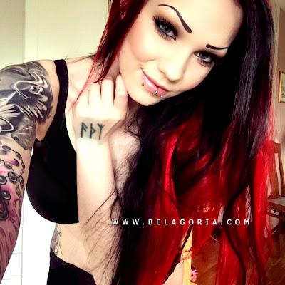 Vemos una mujer de pelo rojo muy sexy, lleva el tatuaje de runas en la mano