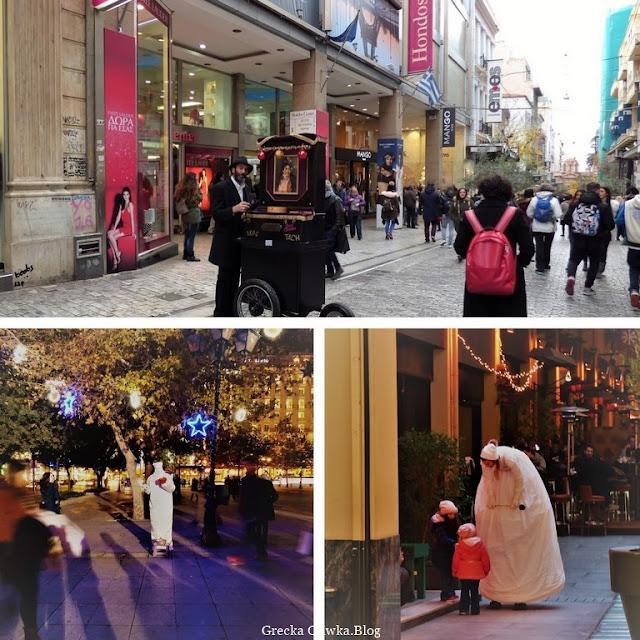 na ulicy: kataryniarz w czarnym ubraniu i kapeluszu, kobieta na szczudłach w białej sukni wróżki, pantomimiarz ubrany na biało, małe dzieci Ateny