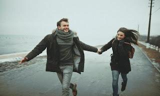صورة رومانسية لعاشقين يجريان و أيديهما متشابكة