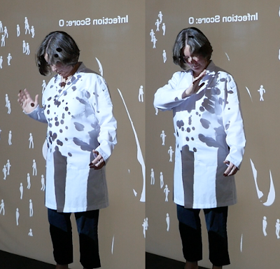 Alison Humphrey in a lab coat playing the full-body videogame Shadowpox: The Antibody Politic at the 70th Assembly of the World Health Organization