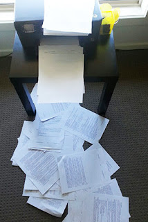 A photograph of papers spilling off the printer and across the floor.