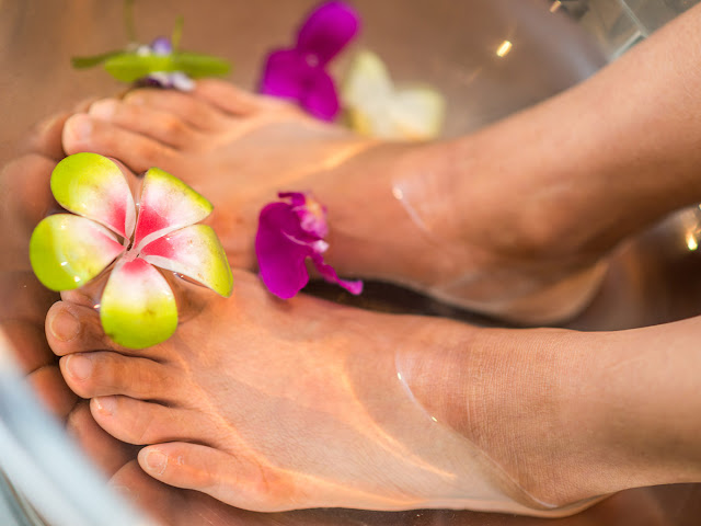 feet being treated in water with floating flowers