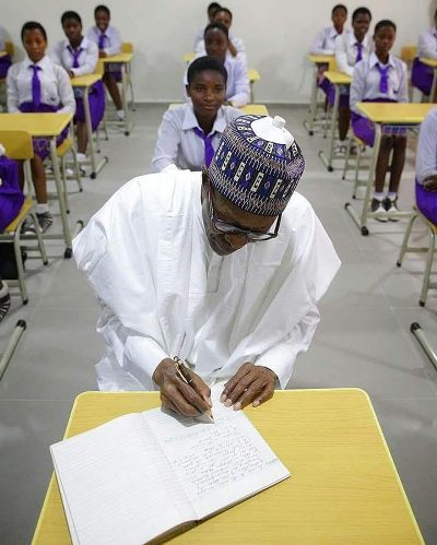 Photo Of The Day: President Buhari Writing Inside A Class Room In Edo State