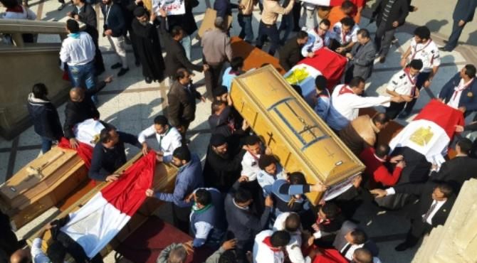 Egyptian clergymen and officials carry the coffins of the victims of a church bombing in Cairo, on December 12, 2016.