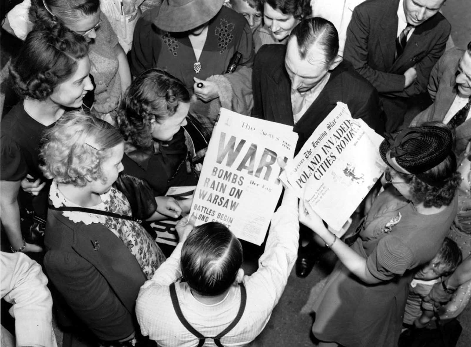 A crowd reads newspaper headlines,