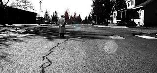 Άντρας με καμπαρντίνα στέκεται στη μέση άδειου δρόμου