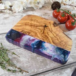 a rippled wood chopping board half dipped in blue, purple, and white swirls