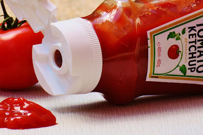 Tomato ketchup bottle, on its side with ketchup spilling out.