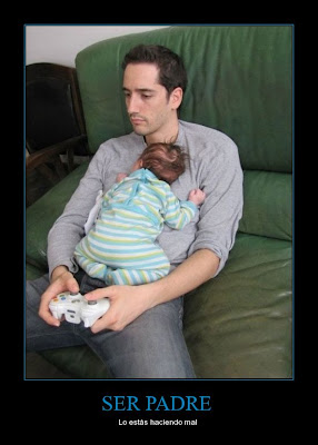 Padre cargando a su bebé y jugando videojuegos