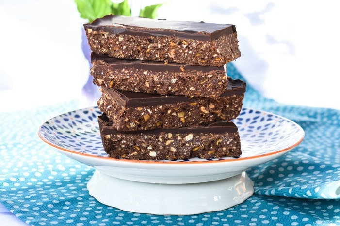 Stack of No Bake Peanut Butter & Cornflake Chocolate Tiffin on blue and white patterned plate