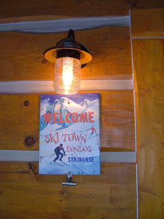"Welcome vintage winter ski sign,  ""Welcome to Ski Town Condos, Staircase"", with an old fashion porch light shinning above."