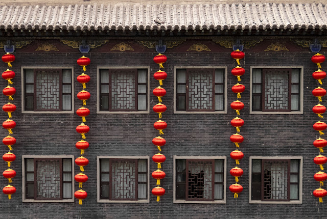 Red lanterns on a grey brick building in Pingyao, China