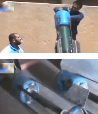 Rebel's in Syria load canisters onto rocket launcher
