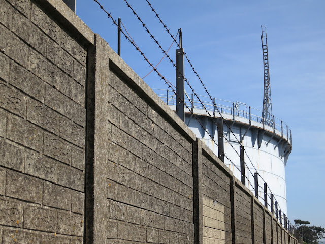 Long grey wall, topped by barbed wire, behind which is lowered gasometer.
