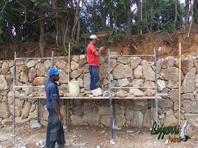 Execução do muro de pedra rústica com pedra do tipo moledo na face do muro e na parte de trás, no enchimento, a pedra rachão. Muro de pedra com os pilares de ferro armado com a cinta de ferro armada a cada 1,50 m de altura.