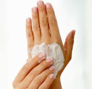 Tratamiento para manos. Dedos de mujer poniendo crema a la otra mano