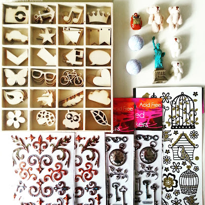 Selection of wooden crafting shapes, dimensional stickers, miniature teddy bears, marble-effect beads plus an owl-shaped bell and miniature Statue of Liberty set out on a desktop.