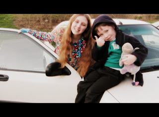 Two children sitting on a white car.