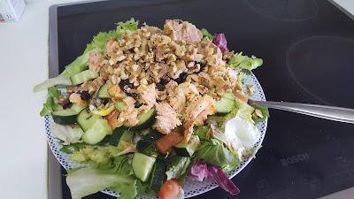 Esta es una ensalada. 4 tipos de lechuga, pepino, tomate, aguacate, nueces, pasas, salmón, atún, aceite de oliva y vinagre